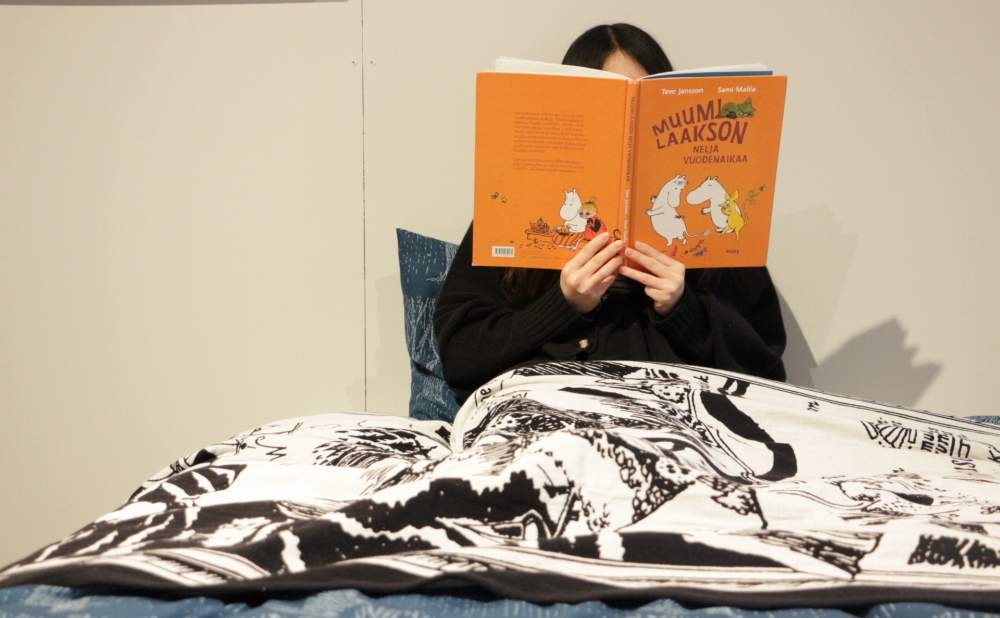 フィンレイソンブランケットムーミン谷マップ2017を膝にかけてベッドに座って本を読む